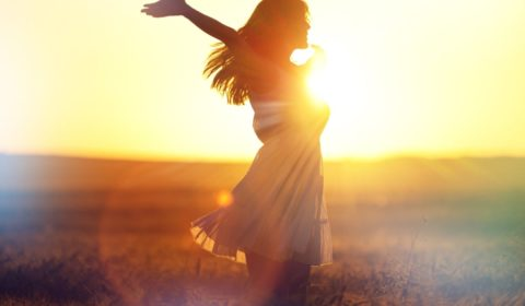 Frau im Sommerkleid Feld Sonnenuntergang Hände zum Himmel