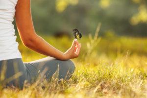 Frau auf einer Wiese meditiert Schmetterling auf der Hand